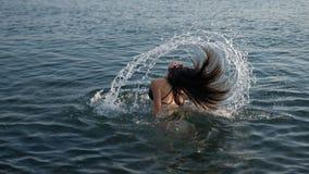 青少年的翻转的头发在水中 库存照片