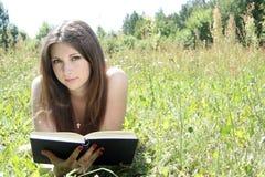 青少年的读取在草甸 免版税库存图片