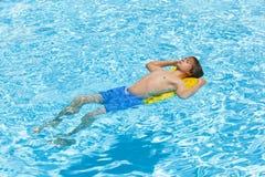 青少年穿蓝衣的男孩跳的池 库存照片