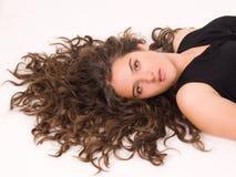 青少年美丽的卷曲的女孩的头发长期 免版税库存照片