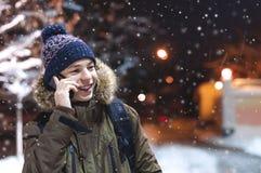 青少年谈话在一条城市街道上的电话在冬天 免版税库存照片