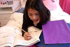 青少年逗人喜爱的执行的家庭作业 库存图片