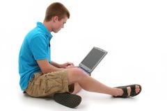 青少年逗人喜爱的有雀斑的膝上型计算机的男 免版税库存图片