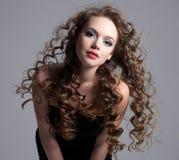 青少年长期卷曲表面女孩魅力的头发 免版税图库摄影