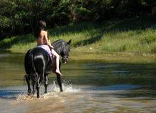 青少年骑马的河 免版税库存照片