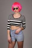 青少年与圈子太阳镜和桃红色头发摆在 关闭 灰色背景 免版税库存照片