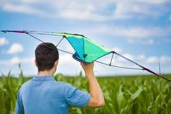 青少年与在麦地的风筝 免版税库存图片