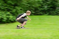 青少年人快速的乘驾一个滑板在公园 库存图片