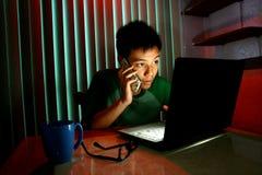 青少年使用一个手机或智能手机在便携式计算机前面 库存照片