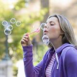 青少年吹的泡影的女孩 免版税库存照片
