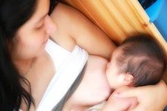 青少年哺乳的婴儿的母亲 免版税库存图片