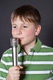 青少年唱歌到话筒 免版税库存照片