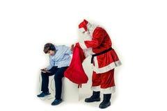 青少年忽略圣诞老人,带来礼物 图库摄影