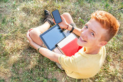 青少年是与片剂计算机和巧妙的电话 免版税库存图片