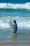 青少年海运的冲浪板 免版税库存照片