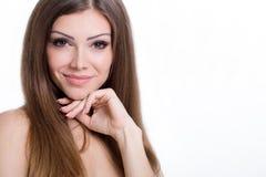 青少年的与在白色背景隔绝的美丽的明亮的棕色长的头发的女孩快乐的享用的秀丽画象 图库摄影