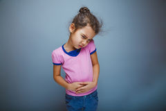青少年的在灰色背景的女孩儿童胃肠痛苦 库存图片