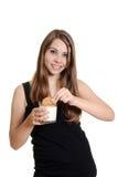 青少年的在牛奶的女孩泡的麦甜饼 免版税库存照片