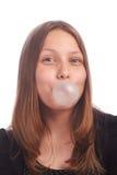 青少年的在白色背景的女孩吹的泡影 免版税库存照片