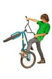 青少年的在自行车的男孩尝试的特技 免版税库存图片