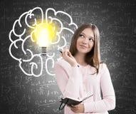 青少年的女孩、大脑子和电灯泡,黑板 图库摄影