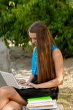 青少年的女孩与在耳机和书的膝上型计算机一起使用 库存图片