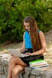 青少年的女孩与在耳机和书的膝上型计算机一起使用 免版税库存照片