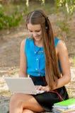 青少年的女孩与在耳机和书的膝上型计算机一起使用 图库摄影