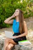 青少年的女孩与在耳机和书的膝上型计算机一起使用 库存照片