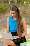 青少年的女孩与在耳机和书的膝上型计算机一起使用 免版税图库摄影