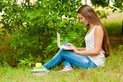 青少年的女孩与在草的膝上型计算机一起使用 免版税图库摄影
