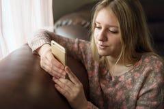 青少年的女孩享用巧妙的电话 免版税库存图片
