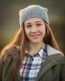 青少年的女孩佩带的帽子和微笑秘密审议 库存图片