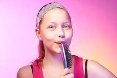 青少年的女孩使用象microphon的发刷 免版税库存照片