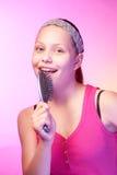 青少年的女孩使用象microphon的发刷 库存照片