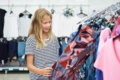 青少年的女孩在商店选择礼服 免版税库存图片
