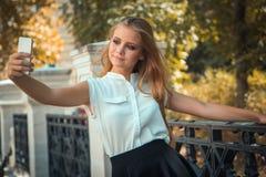 青少年的女孩在秋天公园采取selfie 免版税库存图片