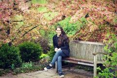 青少年的女孩坐与山楂子开花的长凳 图库摄影