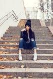青少年的女孩坐台阶对难看的东西墙壁 库存照片