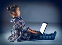 青少年的女孩坐演奏膝上型计算机的地板 免版税库存照片