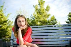 青少年的女孩坐的外部有关的认为 免版税图库摄影