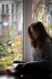 青少年的女孩坐窗台 免版税图库摄影