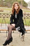 青少年的女孩坐长凳 库存照片