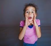 青少年的女孩打开了她的在灰色的嘴电话 库存照片