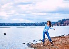 青少年的女孩投掷的岩石在水中,沿岩石湖岸 免版税库存图片