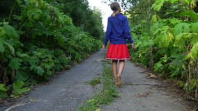 青少年的女孩沿hogweed长满的被放弃的路前进 股票视频