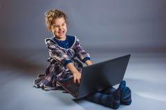 青少年的女孩演奏膝上型计算机的地板惊奇  免版税库存照片