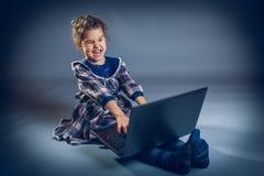 青少年的女孩演奏膝上型计算机的地板惊奇  免版税图库摄影