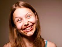 青少年的女孩用在她的面孔的巧克力 库存图片