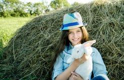 青少年的女孩用坐在干草堆前面的白色兔子 库存照片